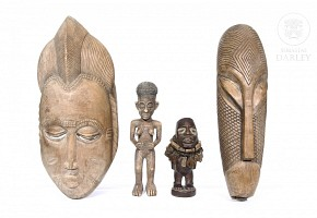 Two figures and two African masks.