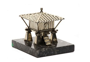 Silver sculpture of a raised granary on a black marble base.