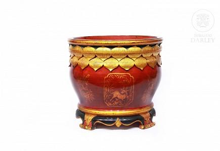 Macetero de madera pintada de color rojo y dorado.