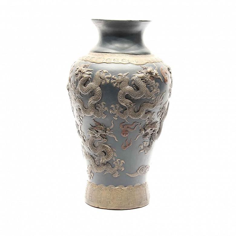 Jarrón de cerámica china con dragones en relieve y fondo azul.
